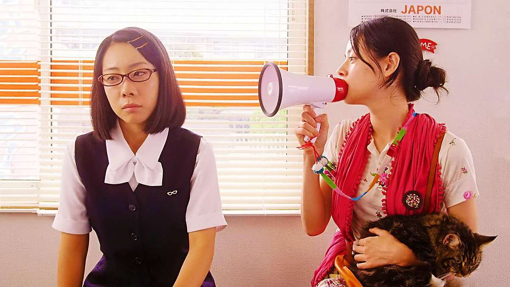 Mikako Ichikawa holds a megaphone to a girl's ear, from the movie Rent-a-cat by Naoko Ogigami