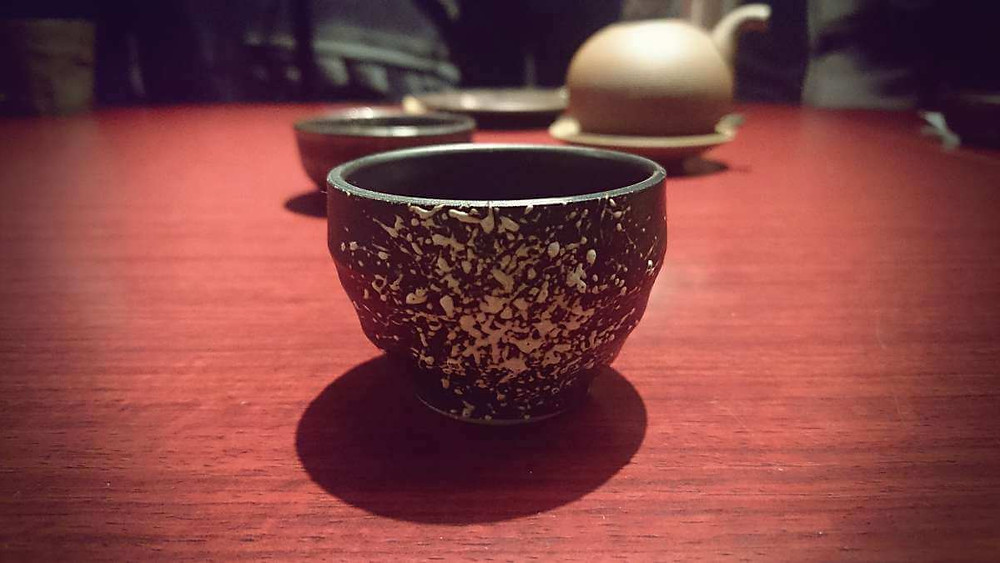Close-up of a sake cup at a Japanese izakaya.