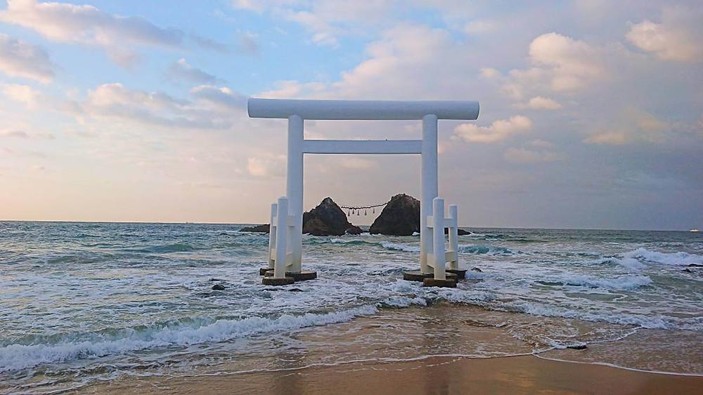 Sakurai Futamigaura: A white Tori Gate on a Japanese beach at Sunset.