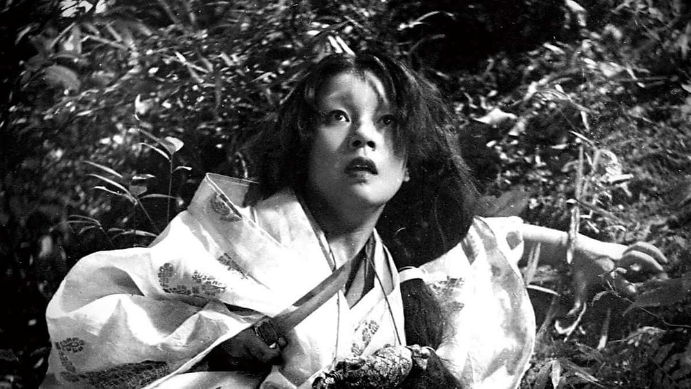 A woman looks terrified while holding a sharp blade in one hand. Taken from the film Rashomon, by Akira Kurosawa.