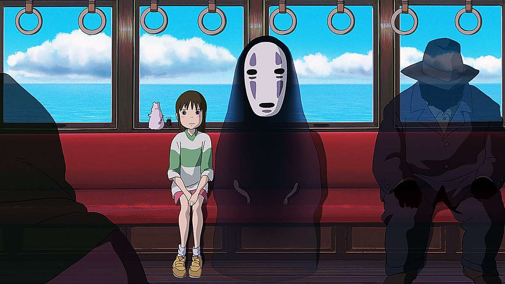 Chihiro and No-Face sitting on the train. Taken from the anime film Spirited Away.