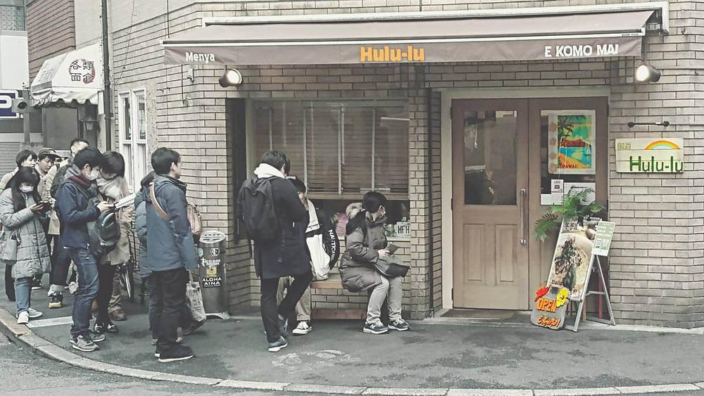 Outside Hulu-lu ramen bar in Ikebukuro, Tokyo. A line of people are waiting to be served.