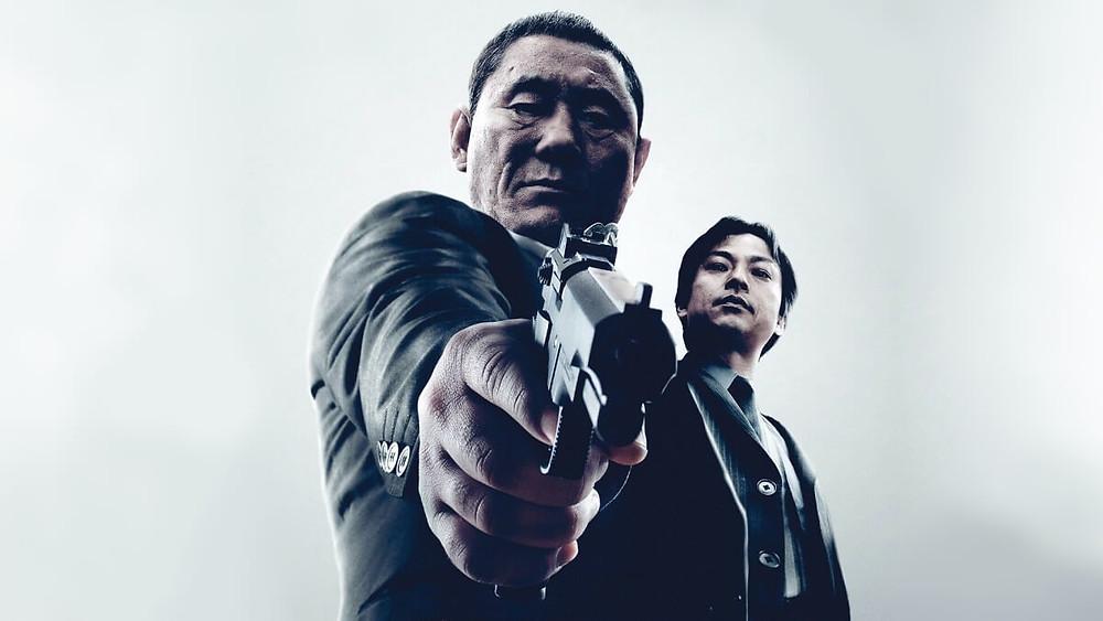 Kitano holding a gun in the yakuza film outrage