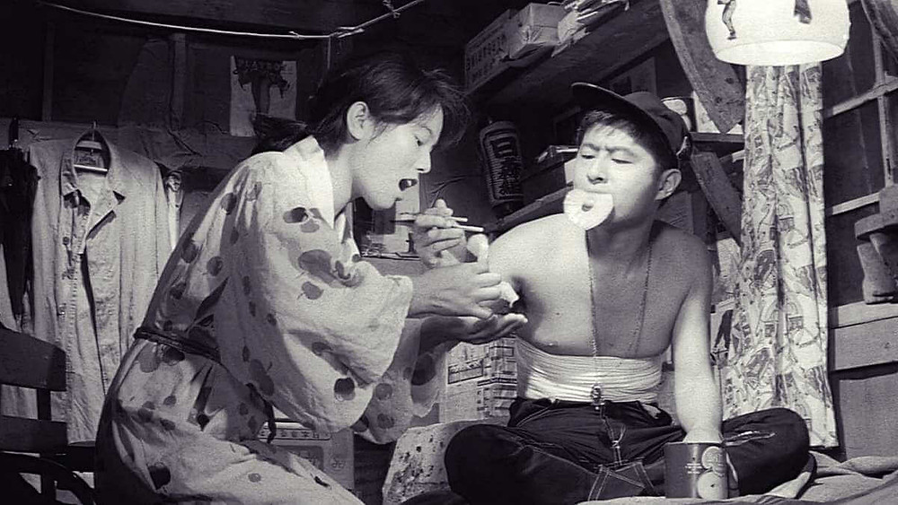 A young couple eating pineapple from a tin in postwar Japan. From the film «Pigs and Battleships» (1961).