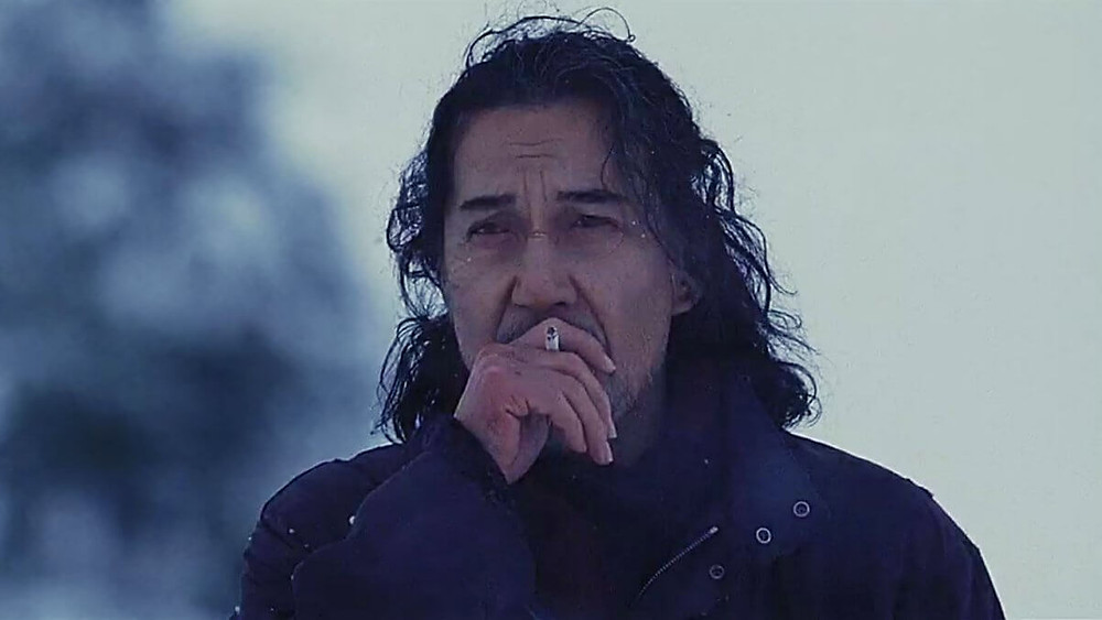 A man smoking a cigarette in the snow. (Still of actor Koji Yakusho, from the movie The World of Kanako.)