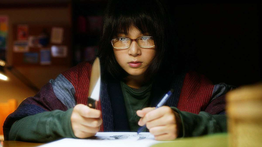 A girl sits at her desk with a knife in one hand and a pen in the other. Taken from the film «Funuke: Show some love, you losers!»