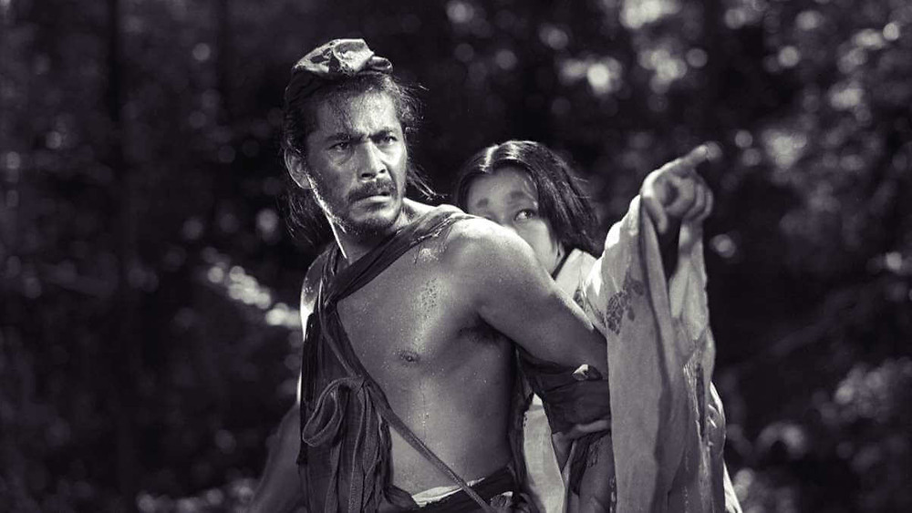 Toshiro Mifune looks angrily in the direction of where a woman is pointing. Taken from the film Rashomon, by Akira Kurosawa.
