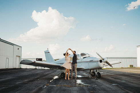 travel couple dancing in front of an airplane