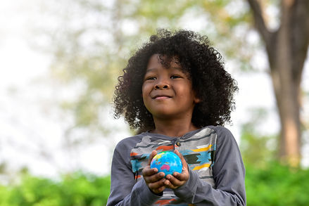 Mixed race boy holding Earth in hands ag