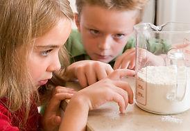 girl and boy measuring flour.jpg