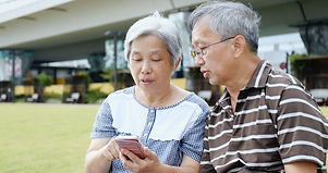 Retired couple using mobile phone togeth