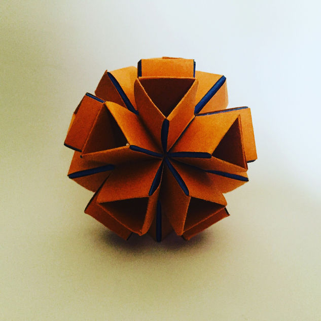 Modular origami. Made up of a number of the same-shaped, interlocking pieces. Look great. Took an age to make. This shape was made using a concept called 'snapology'.