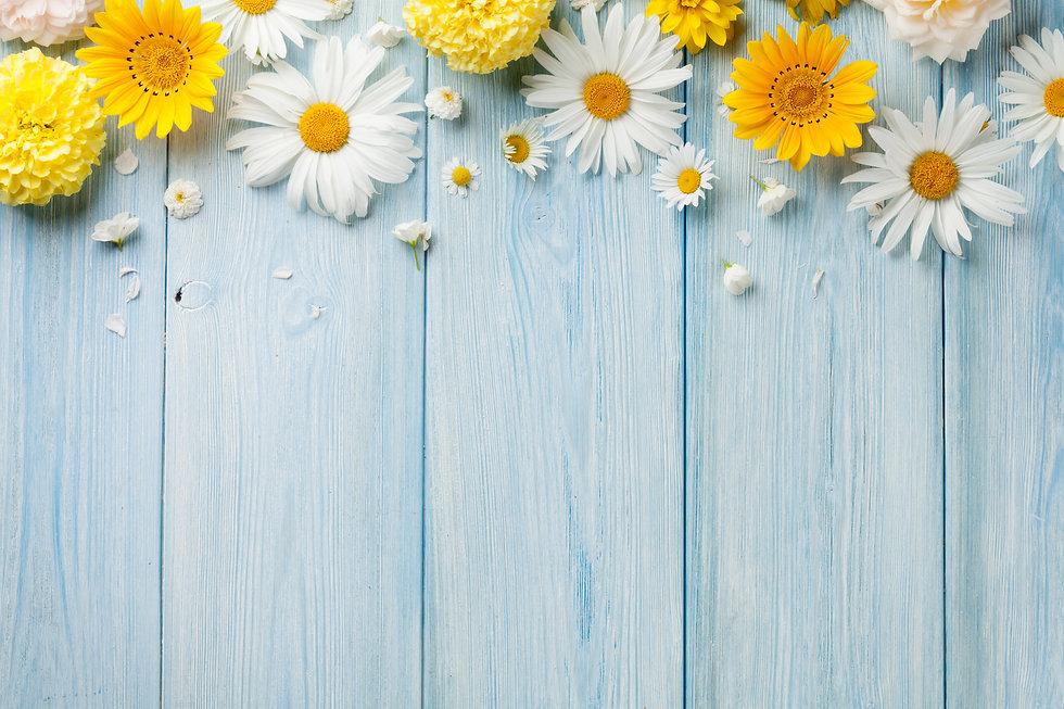Garden flowers over blue wooden table ba