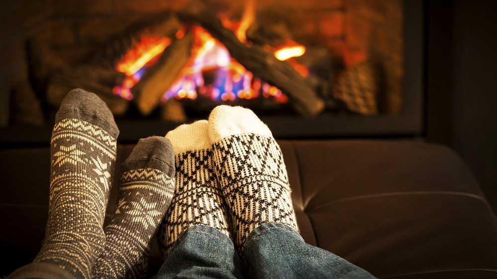 Two feet in socks sit by a fire getting warm during cold months