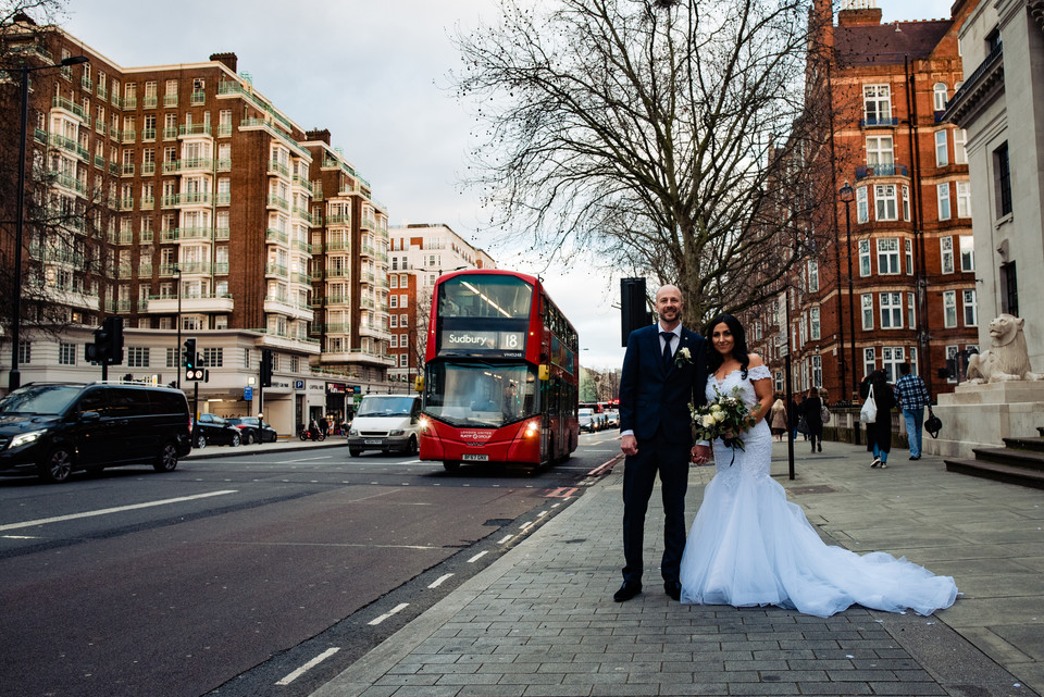 couple embracing and London bus in the background