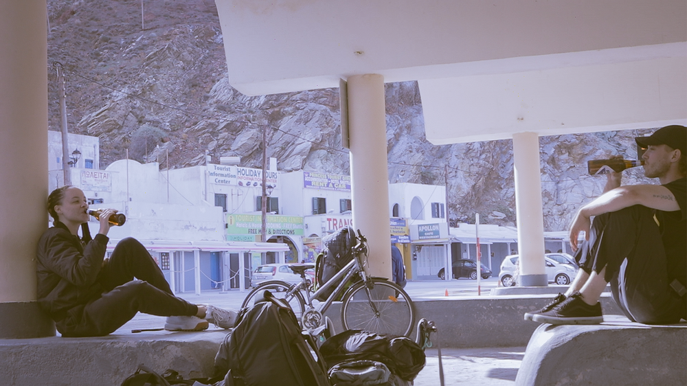 Two people waiting at the Santorini port in Greece for the ferry