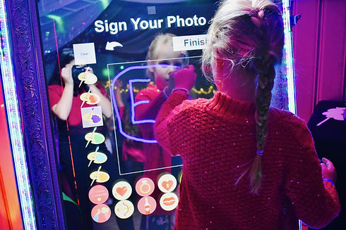 child drawing on a magic mirror photo booth for kids parties in Hertfordshire - Moji Entertainer