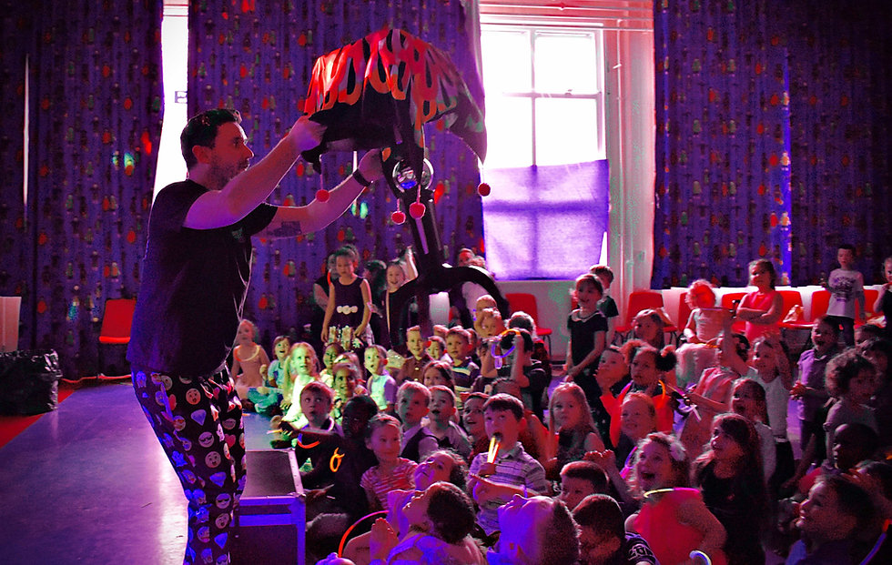 magician performing a flying table trick at a school disco - MMENT
