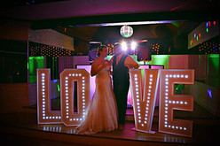 A bride and groom standing next to big light up letters - light up letter hire Essex - MMENT