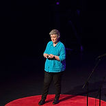 Picture shows Jenni Atkinson in the spotlight on stage delivering a TEDX talk about gender diverse people in 2016 - click on the image to see / hear the TEDX talk