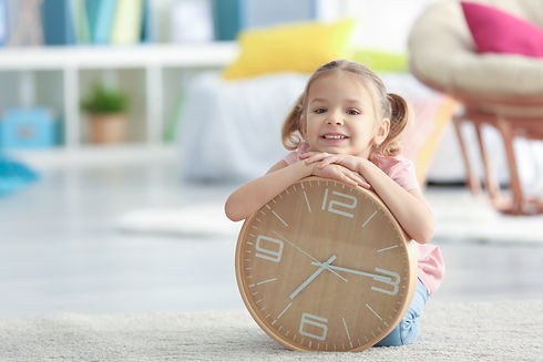 Cute little girl with big clock sitting
