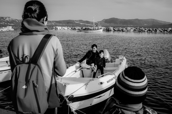 """Father and son, refugees from Pakistan staying in the Moria camp, pose for a picture on someone's boat, after a meal  in a Greek couple's (Katerina and Nikos) restaurant/NGO, """"Home for All""""."""