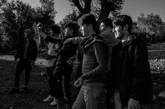 A group of boys playing sangirag - a traditional Hazaragi game - throwing stones at another stone located several dozen meters away.