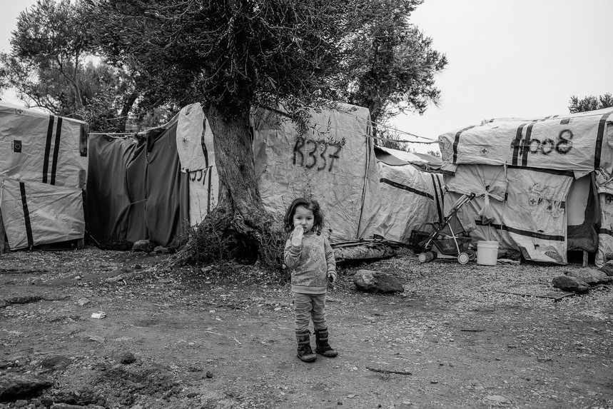 Little girl among the tents in so-called jungle just outside of the Moria refugee camp.