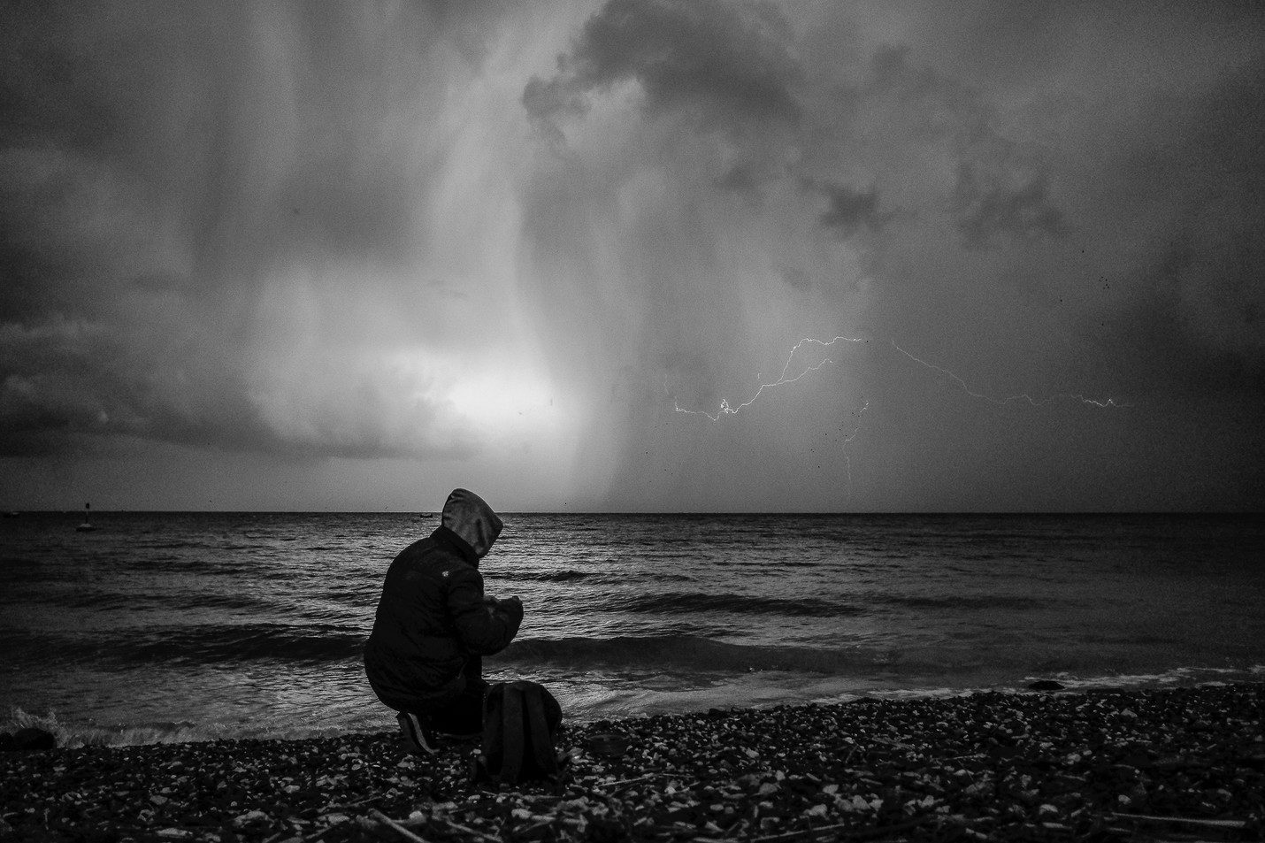 Shahram (14), an Afghan boy, fishing on the shore just outside of Mytilene, during a massive storm.