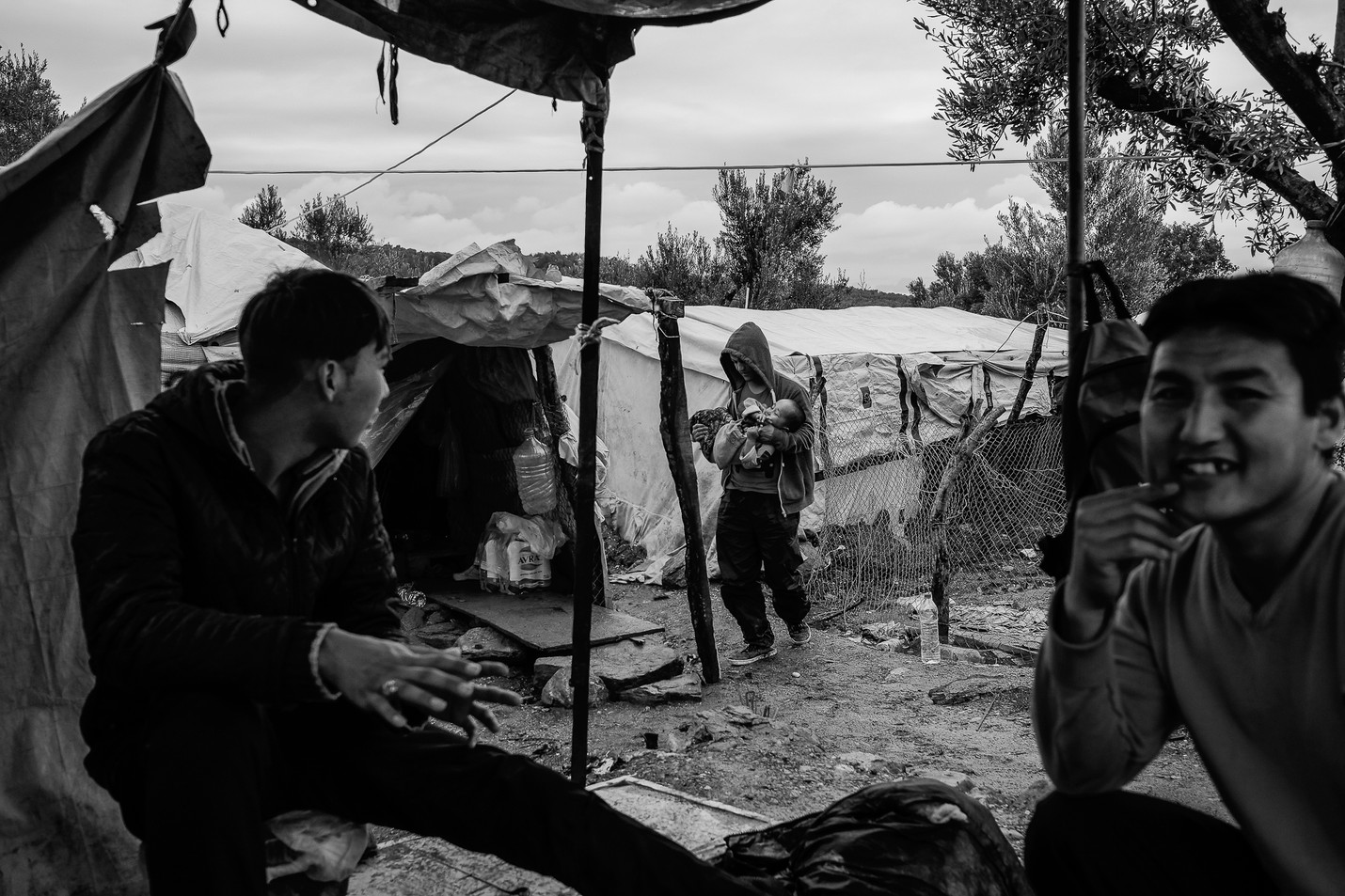By the fire with Hasan (30) from Afghanistan (right) and his relatives among their tents in the so-called jungle just outside of the Moria refugee camp.
