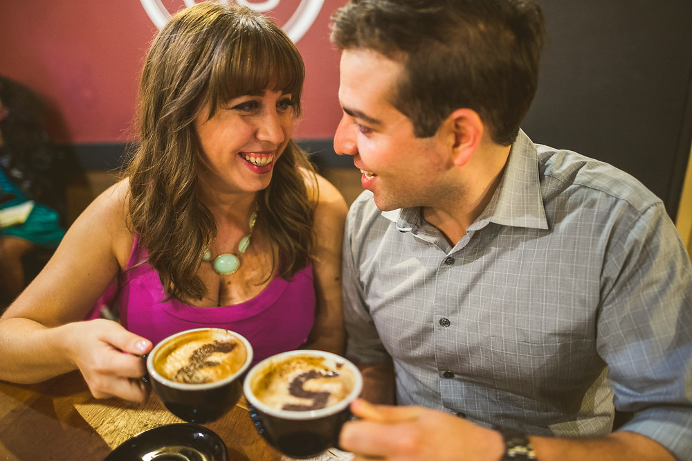 Megan and Gregory drinking coffee during their engagement photo shoot.