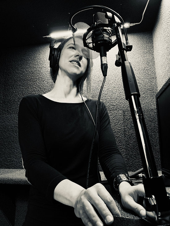 Juliana in her studio, speaking into her AT4040 Audio-Technica Studio Mic that she uses for her Spanish voiceover projects.