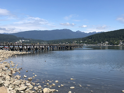 The pier at Rocky Point Park in Port Moody, BC with the waters of Burrard Inlet in the foreground and mountains in the background.