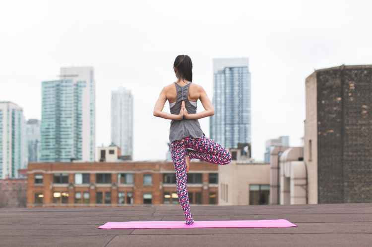 A woman standing on one leg on a pink yoga mat, on a roof of a building with a skyline in the background as she meditates.
