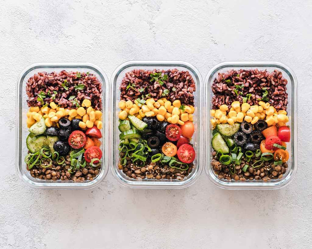 Three glass containers with rice, lentils and vegetables, which is a healthier option when heating food than plastic containers.