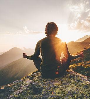 Man meditating yoga at sunset mountains