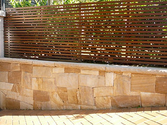Sandstone wall with fence and driveway