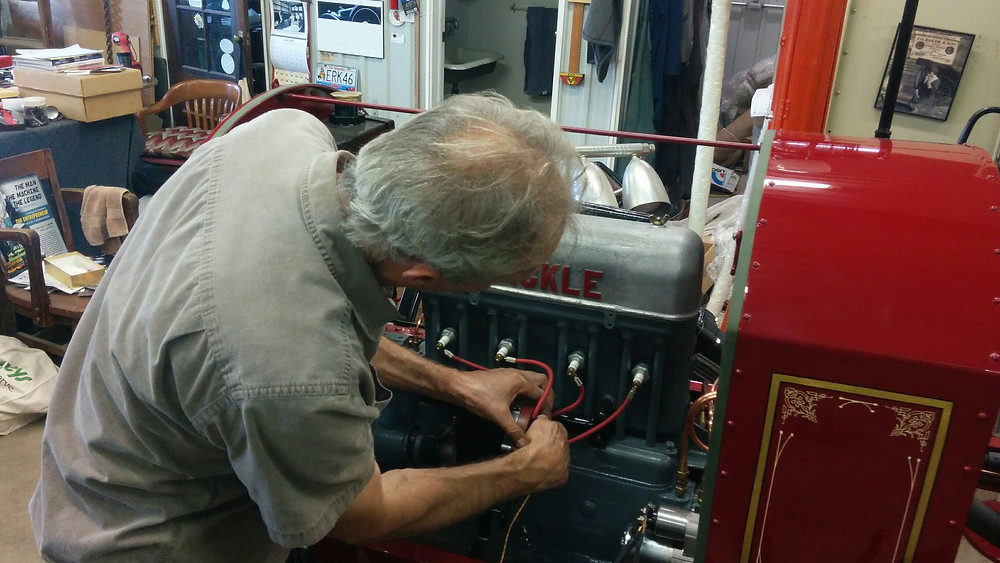 Stan Uher checks the plug wires on his latest restored classic - a 1917 Bickle Pumper