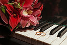 flower and wedding rings on piano keys