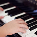 hands playing piano keys