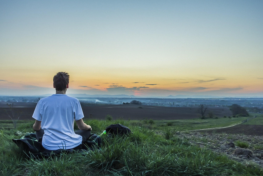 A man sitting outside meditating or sitting peacefully looking out at the horizon.