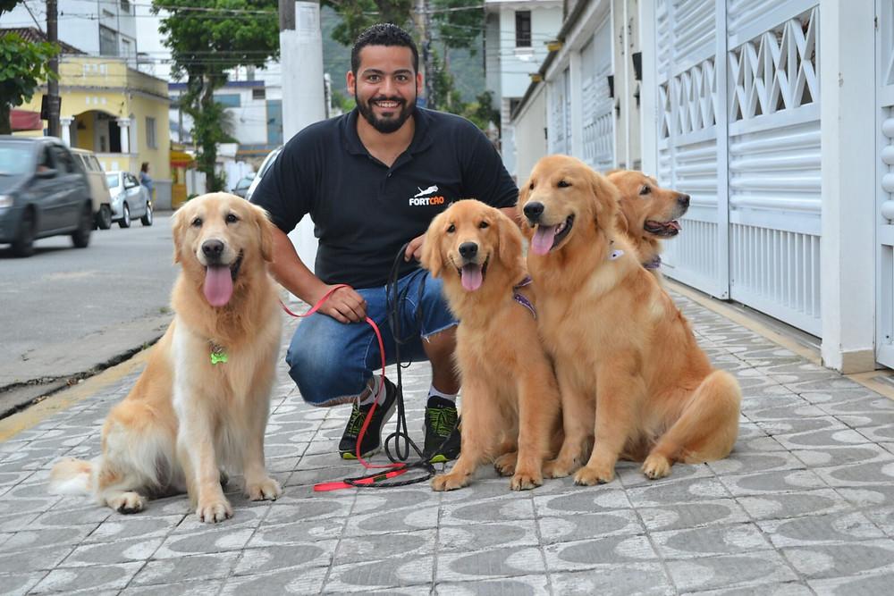 Felipe Pandolfo com quatro lindos cães da raça Golden Retrivier. Os cães estão sentados e Felipe está agachado entre eles. A foto foi tirada durante um passeio com os cães. Todos estão muito felizes.