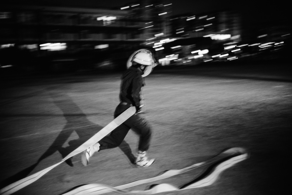 Member Furuya Kazuyuki (41) runs with two hoses, which he will connect to create a single longer one.
