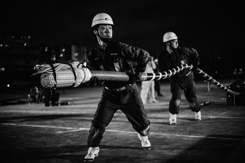 Members Masafumi Sato and Asaya Tomoyuki move a large water hose into position.