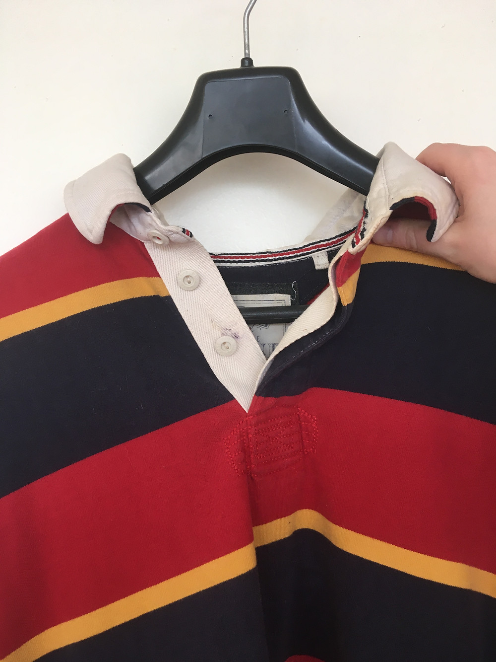 A red, yellow and black striped shirt on a coat hanger, being held up by a hand.