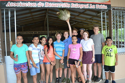 Visiting and local students with a sloth