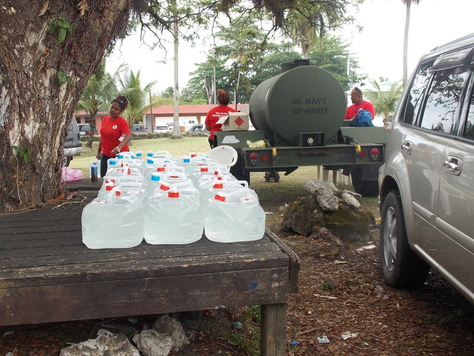 Red Cross volunteers fill up jerry cans for water distribution. Photo by Imelda Mai (Facebook)