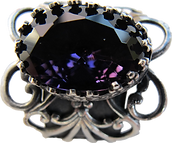 'Flower Ring 2' is created by the artist Beate Nyfløt. Faceted amethyst glass stone in 525 sterling silver crown setting. The decor is silver plated brass filigree. The ring is 525 sterling silver.