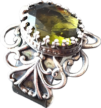 'Flower Ring 1' is created by the artist Beate Nyfløt. Faceted olive-green glass stone in 525 sterling silver crown setting. The decor is silver plated brass filigree. The ring is 525 sterling silver.