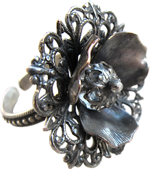 'Flower Ring 12' is created by the artist Beate Nyfløt. The stone is faceted swarovski crystal bead. The decor is silver plated brass filigree. The ring is 525 sterling silver.